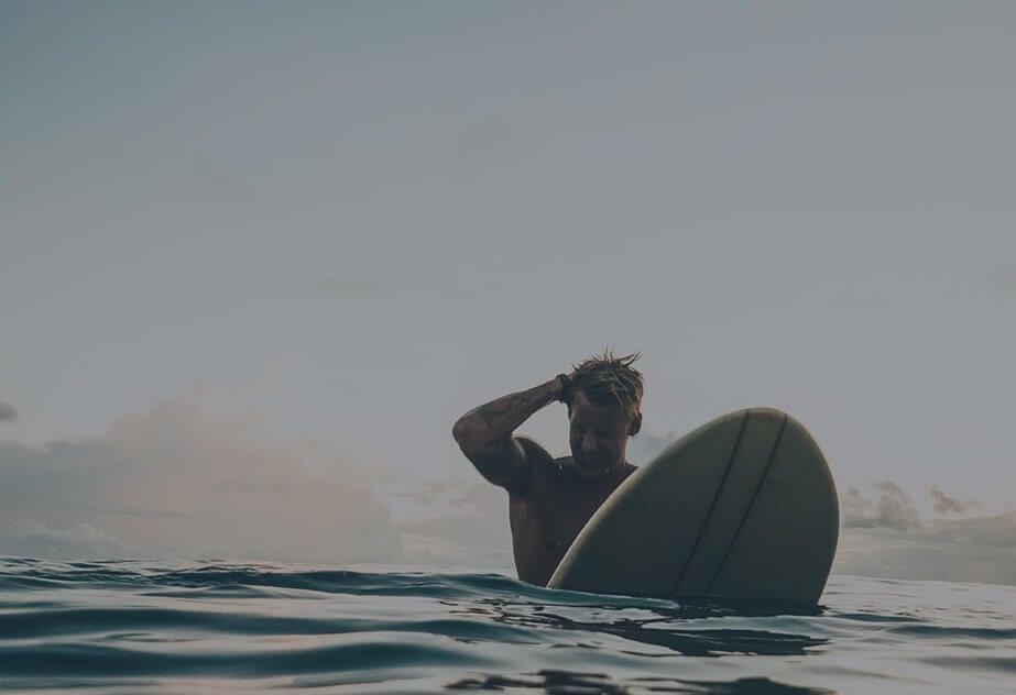 Men in sea water with surfboad in hands