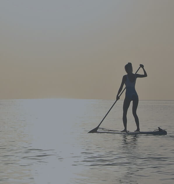 Girl surfing on a small raft paddles with an oar