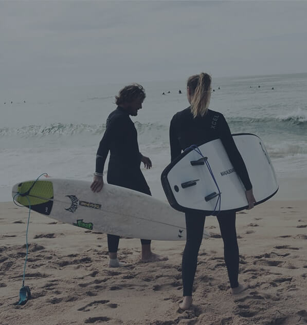 Couple wearing black wetsuit walking on a beach with surfboard in hands