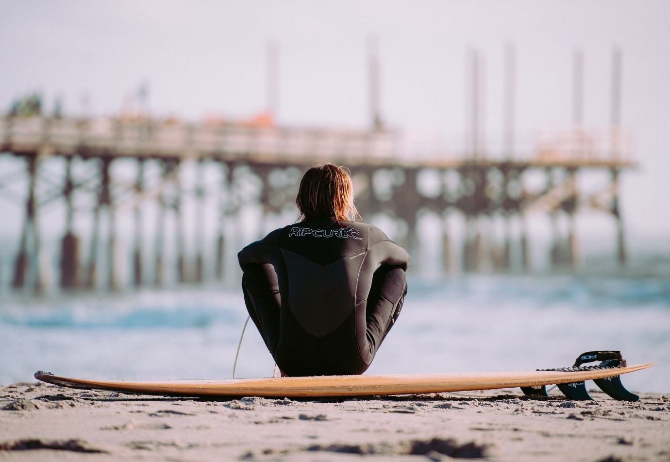 Men in a black wetsuit seated outside beach with a shortboard surfboard