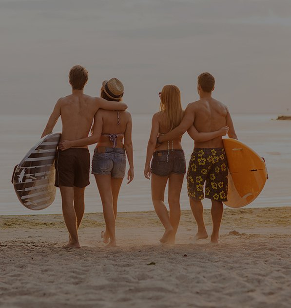 Couples on beach enjoying with surfboards in hands