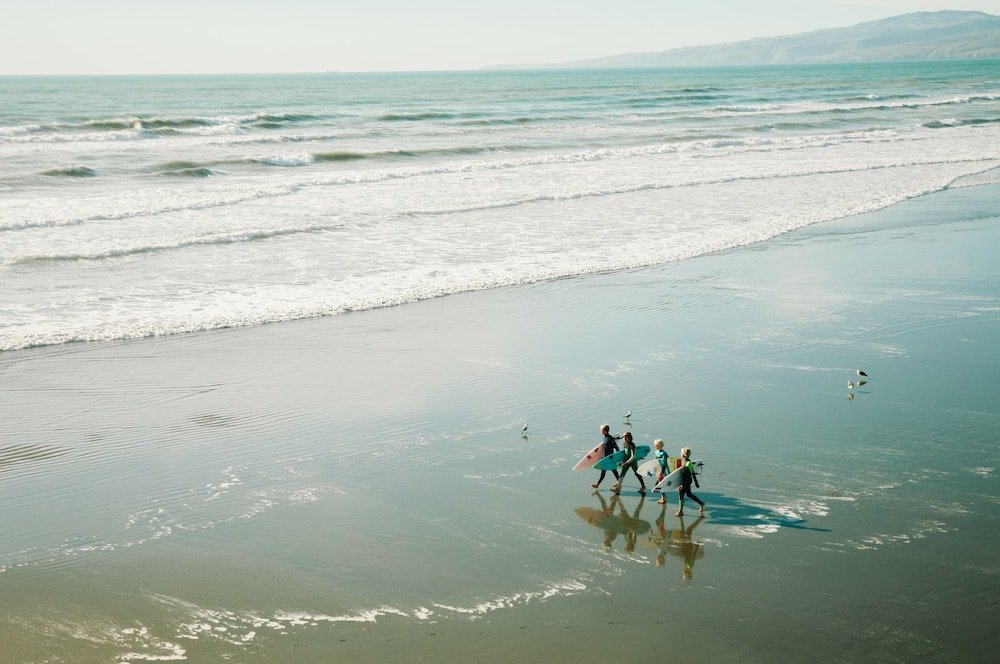 A group of groms and older surfers walking on the beach with surfboards