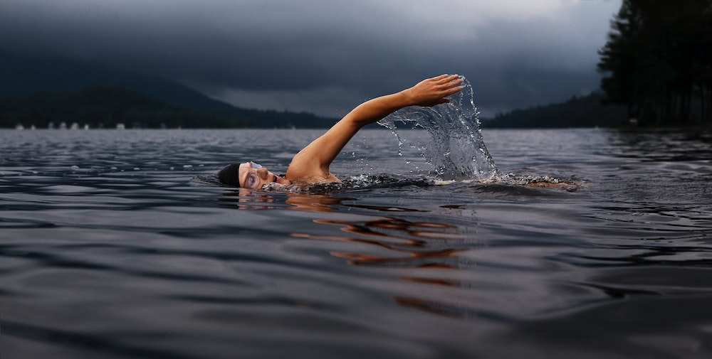 A woman open water swimming with arm raised out of the water