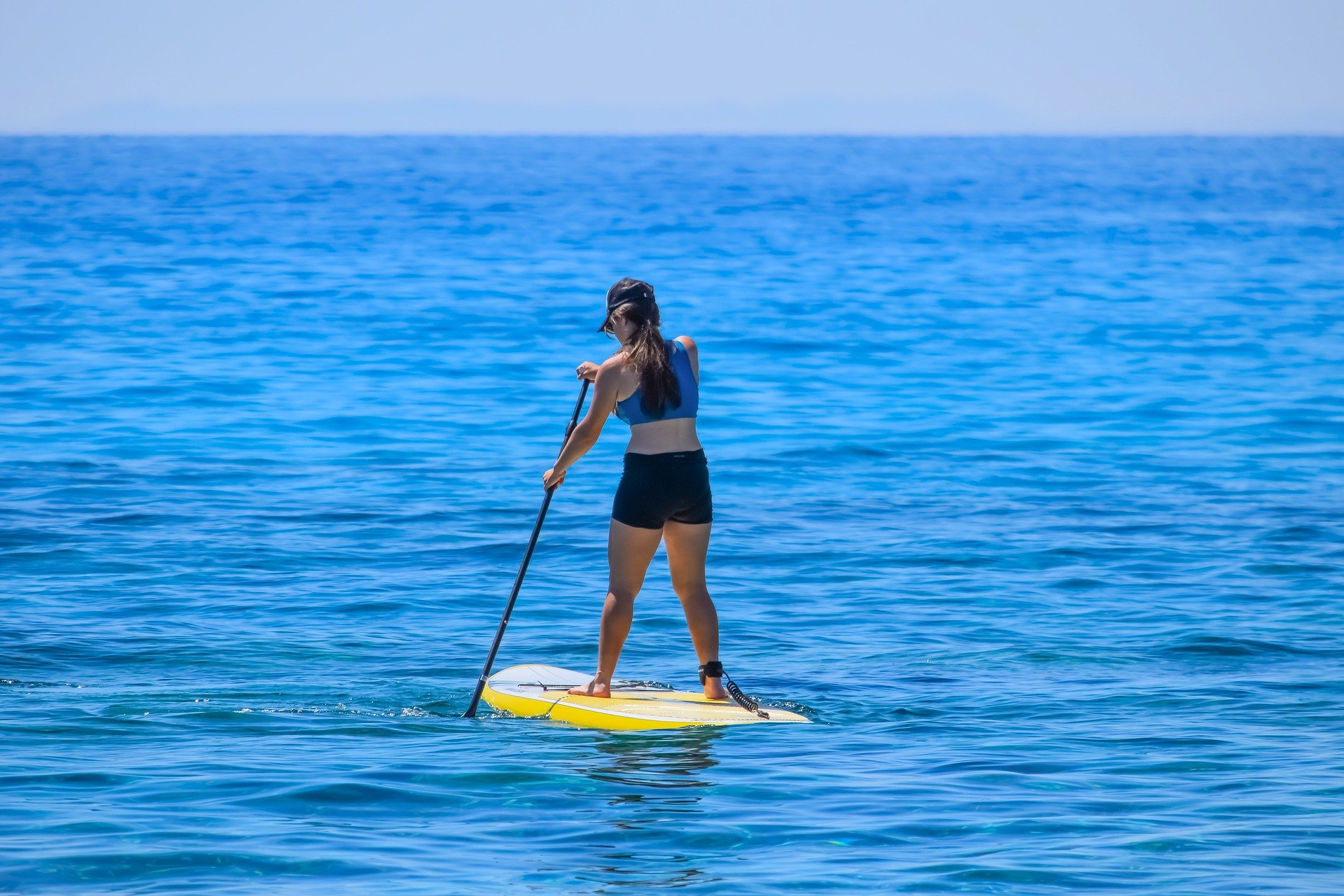 Girl doing paddleBoarding in beautiful summer weather