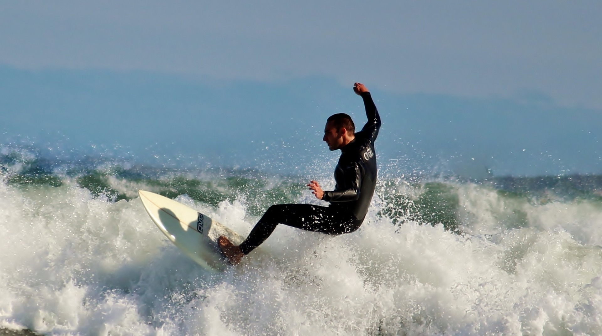Men enjoying surfing on high waves with a comfortable wetsuit
